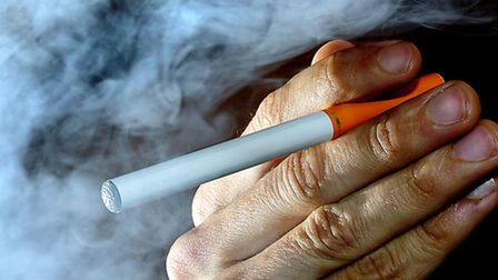 PICTURE POSED BY MODEL A person smokes an electronic cigarette, or e-cigarette.