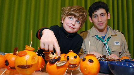 Alexander (five) makes a creature out of oranges and dried fruit helped by a member of the Israeli S