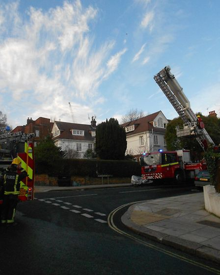 Firefighters use an aerial ladder as they tackle the blaze in Kidderpore Avenue, Hampstead, this aft