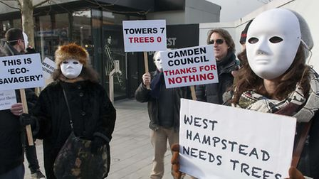 Masked and unmasked campaigners outside Ballymore sales office in West End Lane mourn the loss of tr