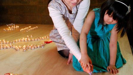 Katsura Danno and daughter June, 5, light candles to remember victims of the Japanese tsunami. Pictu
