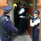 Police enter the former Hampstead police station as squatters begin to come out with suitcases