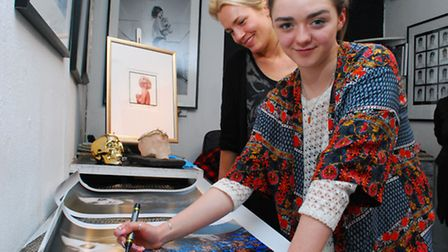 Actress Maisie Williams signs a portrait of herself at Zebra One Gallery in Hampstead with gallery o