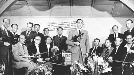 Members of the Westerbork transit camp string orchestra pose on stage with their instruments. Dutch