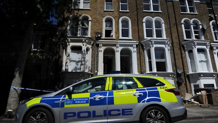 Police seal off a building after a man fell to his death from a first floor window this morning