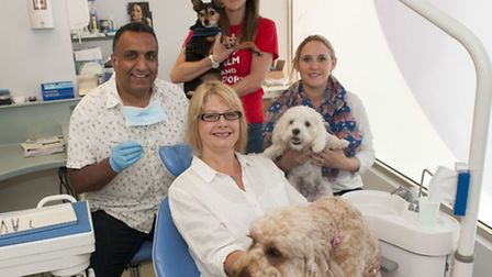 Dr Jay Prashar and his wife Irene in the dentist's chair with their pet dog Toffee. Back, left to ri