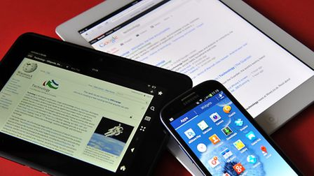 Stock photo of an Apple iPad, a Kindle HD and a Samsung Galaxy S3 android phone.