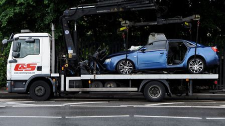The wrechage of a car that crashed with a bus is put onto a tow truck Photo: David Mirzoeff