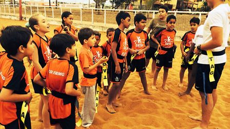 Nick Gourlay (right) introduces Brazilian youngsters to tag rugby on the beach