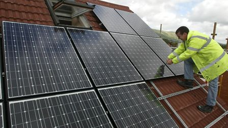 Solar panels being installed on the roof of a building. PA Photo/Niall Carson