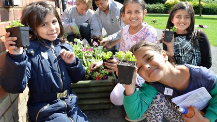 Members of the Harrington Scheme help children to plant in beds around the cafe, from left: Rukhsar,