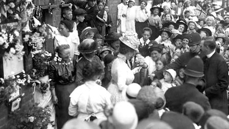 Queen Mary distributes some of her flowers to children after viewing a roll of honour on Palace Road
