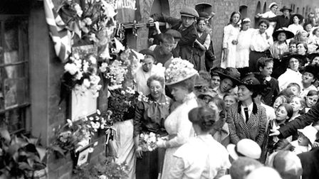 Queen Mary reads a roll of honour during a visit to Palace Road in Hackney.