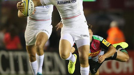 Alex Goode breaks with the ball against Harlequins as Saracens team-mate Will Fraser looks on. Photo