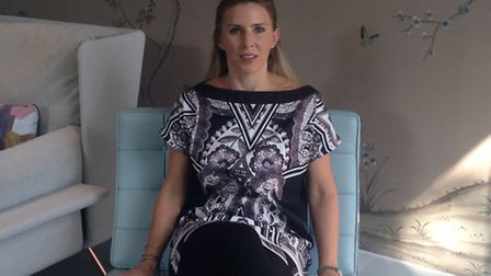 Carly Madhvani of NW3 Interiors sitting on her Knoll Barcelona chair
