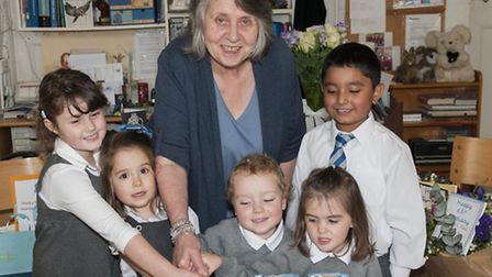 Headteacher Andrea Taylor whose mother founded the school cuts the birthday cake with Elsie, Alexand