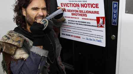 08/11/2014. Russell Brand puts a fake eviction notice on The Benyon Estate office as he joins a grou