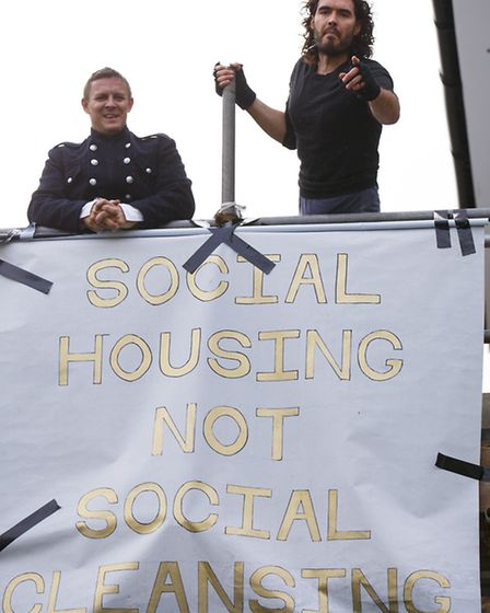08/11/2014. Russell Brand attaches a banner to a The Benyon Estate property's scaffolding as he join