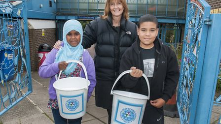 Jude Goodall,10, Sawdah Mohamed, 11, with headteacher Kate Frood collect money at the school gate to