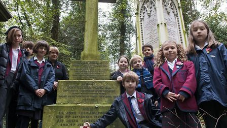 Pupils from Highgate Junior School lay a poppy and cross on the grave of Murray Stuart Pound, a head