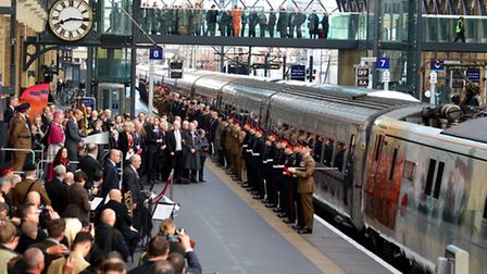 100 serving and veteran military personnel line the platform as the specially liveried Class 91 loco