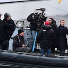 Rory Kinnear and Daniel Craig stand at the front of a speedboat on the canal in Camden, as they fil