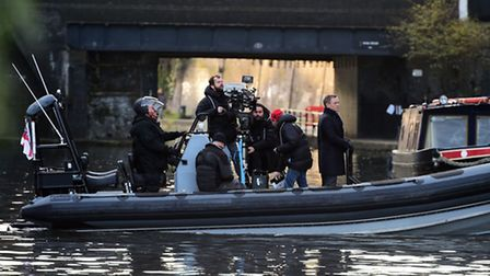Daniel Craig stands at the front of a speedboat on the canal in Camden, as they film scenes for the