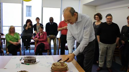Dr John Simmonds celebrates his OBE by cutting a cake made specially by his wife