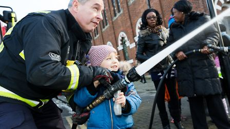 Caanan Cumberbath (aged four) plays with a firemans hose during the Fire Brigade visit to ABC Day Nu