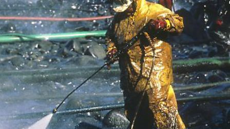 A worker uses a high pressure hose to blast the oiled rocks after the oil spill of the Exxon Valdez.