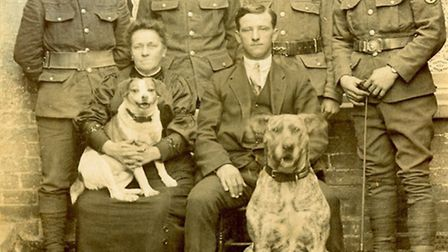 Off to war, August 1, 1915... soldiers behind seated civilians and two family pet dogs