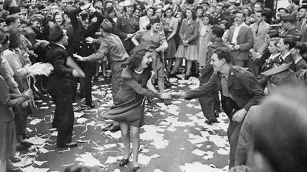 "British girls dance in the street with American soldiers during the ""VE Day"" celebration in London M"