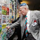 Survivor Jack Hecht, 86, examines his quilt square, created by grandsons Josh and Noah Hecht.