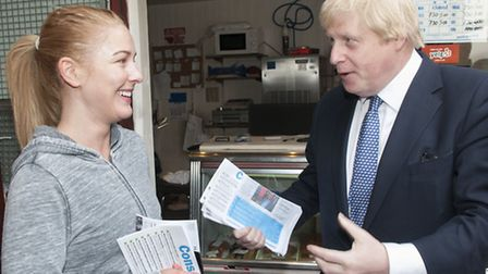 Boris talks housing with jogger Esme Kilsby at a fishmongers off Hampstead High Street
