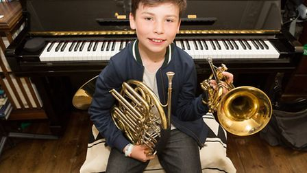 Louis Loddo (aged 11) sits at his piano with his french horn and trumpet.