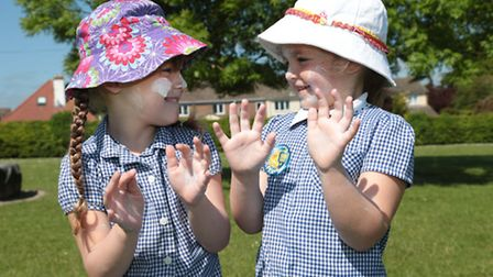 EDITORIAL USE ONLY Lara Mai and Imogen from Tannery Drift Primary School in Royston, apply suncream