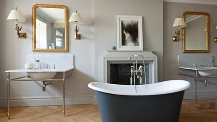 The bathroom features a boat bath, marble basins and lights held by golden mermaids. Picture: Matt