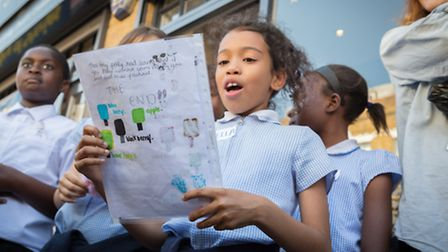 A girl reads her poem at the Ministry of Stories event