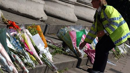 A Police officer lays flowers near the scene of the bus explosion in Tavistock Square.