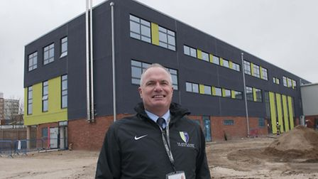 Outgoing headteacher Mick Quigly in front of Archer Academy's new campus due to open in September