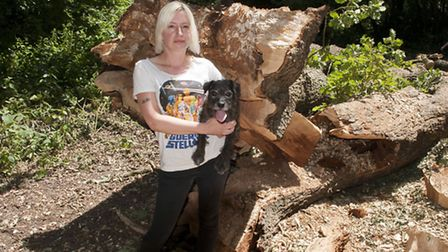 Faye Manswell with dog Gary in front of the tree which fell where she stood