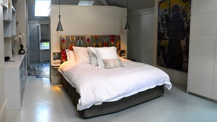 Teague and her husband's open plan bedroom, which features a bathroom on the other side of the parti