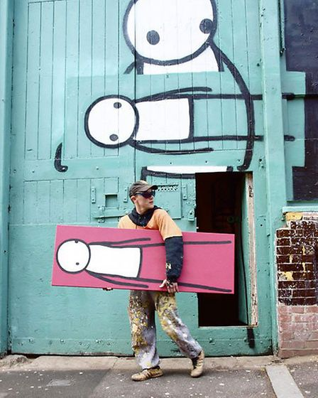 Stik outside his old studio in Pitfield Street, Hackney with the 'moved' stick person symbolising th
