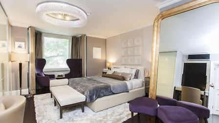The spacious master bedroom with accents of regal purple and gold
