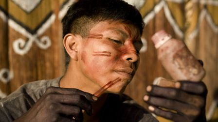 A young barasano tribesman from Colombia paints his face. Picture: Sergio Bartlesman