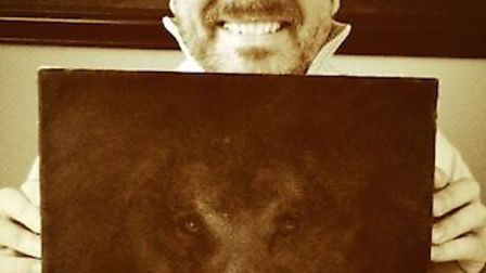 Comedian Ricky Gervais with his painting of a lion