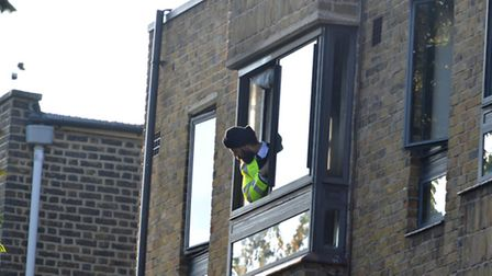 Police Officer looks out of a window at the rear of Ashton Court Camden Road following a fire at the