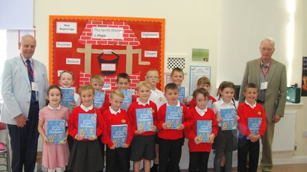 Year 3 pupils at Corton Primary School, flanked by Rotarians Roy James (left) and John Pilling, are presented with their...