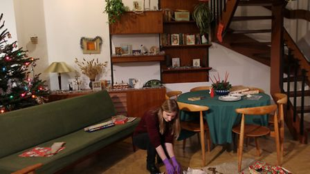 Curator preparing the 1965 period room for the Christmas Past exhibition