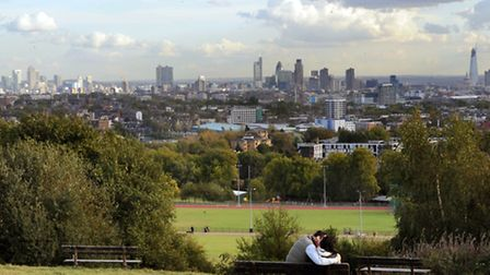 A couple enjoy the view of the London skyline from Parliament Hill, London
